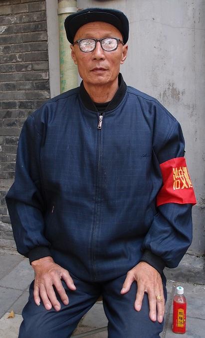Den här mannen sitter på historier. Det ser man. Bild tagen strax utanför Den Förbjudna Staden i Beijing. Han arbetade som volontär för staden och satt vakt utanför en butik.
