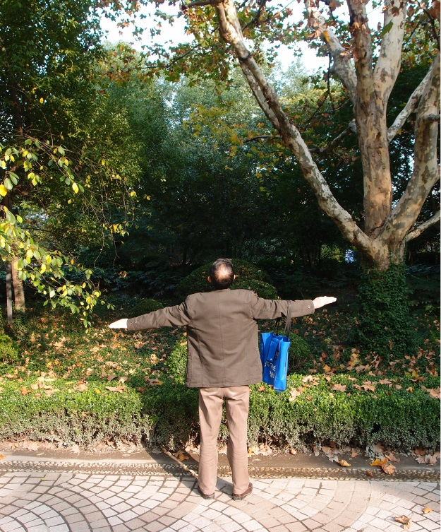 """En man som njuter av eftermiddagssolen i en centralt belägen park i Shanghai. Påminner om Carecas gamla målgest """"Flygplanet""""."""